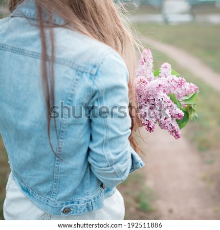 Picture from behind girl in a denim jacket and lilac flowers in their hands - stock photo