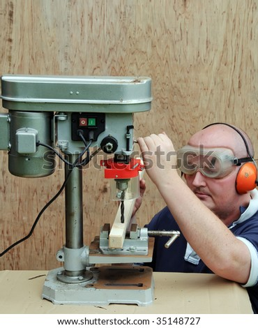 picture male using a drill press on wood - stock photo
