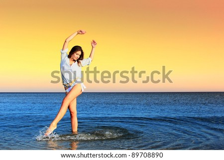 Picture of a beautiful beach in the tropics, with a woman on the beach. Arms raised up in the air and beautiful water ripple
