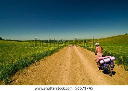 Picture of a bike rider in sunlight field - stock photo
