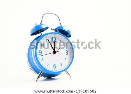 Picture of a blue retro alarm clock on a white background with the clock five to twelve - stock photo