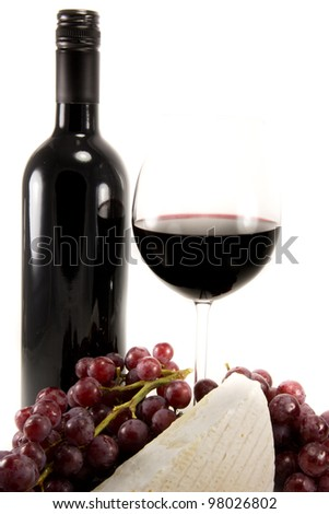 Picture of a bottle of red wine and some brie and a bunch of grapes