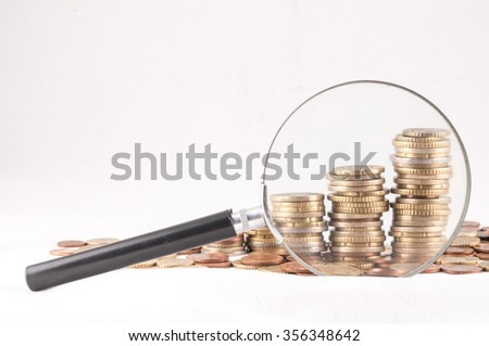 Picture of a Business Money Concept Idea Coins and Loupe Magnify Glass