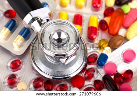Picture of a colourful pills capsules and stethoscope - stock photo