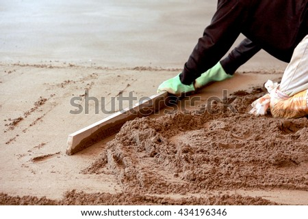 Picture of a Concreting the floor of a house. motion blur on grading tool and hands.