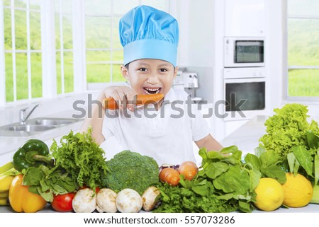 Picture of a cute Asian boy preparing vegetables and eats a carrot in the kitchen at home