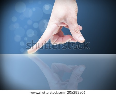 Picture of a finger pointing on a transparent device.