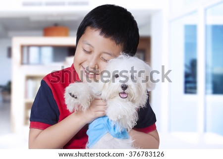Picture of a funny little boy hugging a maltese dog at home while smiling happy - stock photo
