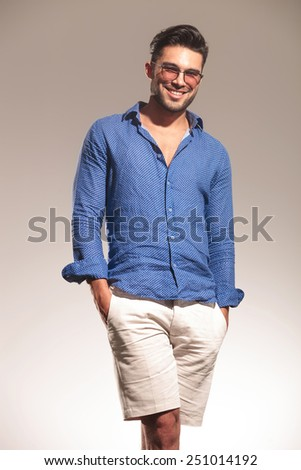 Picture of a handsome young fashion man smiling to the camera with both hands in his pocket. - stock photo