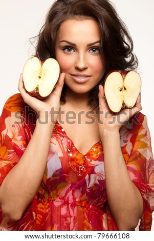 Picture of a happy beautiful woman holding apple halves in hands - stock photo