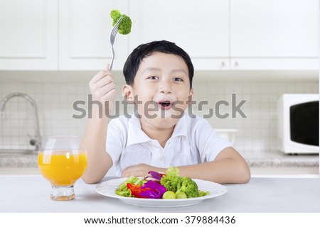 Picture of a little boy sitting in the kitchen and eats vegetable salad with orange juice - stock photo