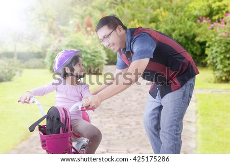 Picture of a little girl and her father learn to ride a bicycle on the path at the park
