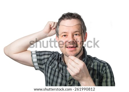 Picture of a man putting on a mask of himself.