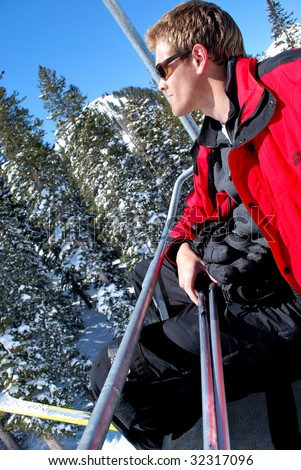 Picture of a man riding up a ski lift on a sunny winter day. - stock photo