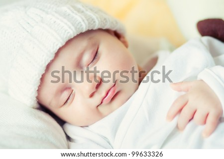 picture of a newborn baby curled up sleeping on a blanket - stock photo
