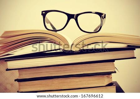 picture of a pile of books and eyeglasses, with a retro effect - stock photo