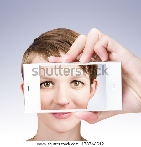 Picture of a pretty woman in twenties taking selfie photo with mobile cellphone on studio grey background - stock photo