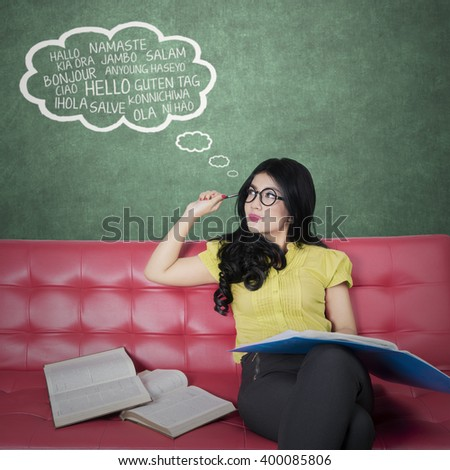 Picture of a pretty woman sitting on the sofa while reading books and learns foreign language - stock photo