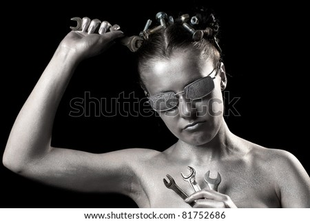 Picture of a robot man with wrenches. Black background. Studio shot.