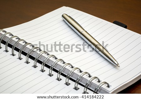 Picture of a silver pen and open spiral notebook lying on a dark brown wooden desk - stock photo
