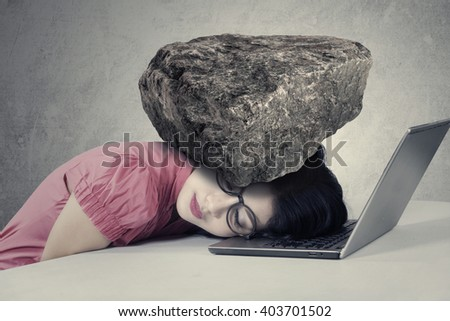 Picture of a stressed businesswoman sleeping over a notebook computer with a burden on her head
