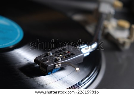 Picture of a vinyl record playing. Blue label and needle