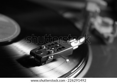 Picture of a vinyl record playing in black and white - stock photo