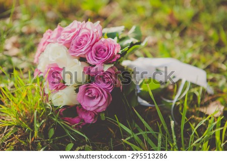 picture of a wedding bouquet, wedding bouquet of pink and white roses lying on grass - stock photo