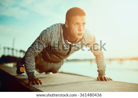 Picture of a young athletic man doing push ups outdoors.Fitness and exercising outdoors urban environment.Selective focus - stock photo