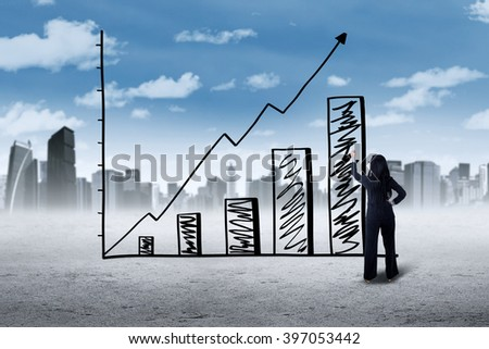 Picture of a young businesswoman making a growing graph with upward arrow, shot outdoors - stock photo