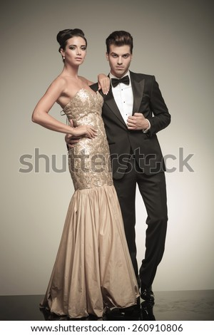 Picture of a young elegant couple posing together, the woman is holding her hand on her waist while the man is fixing his jacket. - stock photo