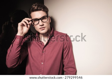 Picture of a young fashion man fixing his glasses while looking away from the camera.