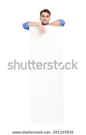Picture of a young handsome man leaning on a white empty banner, while smiling. - stock photo