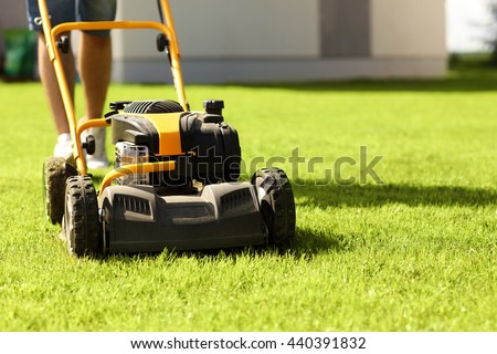 Picture of a young man mowing the lawn - stock photo