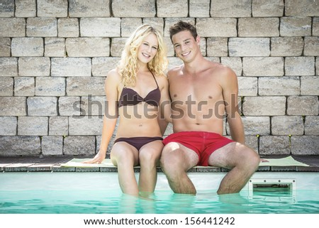 Picture of a young pretty blond girl and a handsome boy with swimwear sitting on the edge of a swimming pool - stock photo