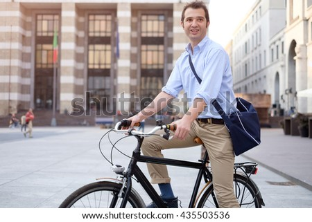 Picture of a young smiling business man on a bicycle on his way home from work while the sun is setting. He has a more relaxed style with the sleeves of his blue shirt rolled up. - stock photo