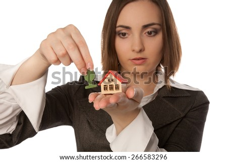 Picture of a young woman planting a toy tree near the toy house focus on house) - stock photo