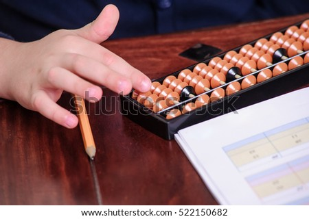 Picture of abacus with child's hand.