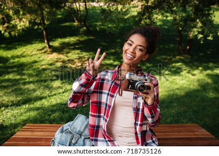 Picture of amazing young african woman photographer sitting outdoors in park. Holding camera.