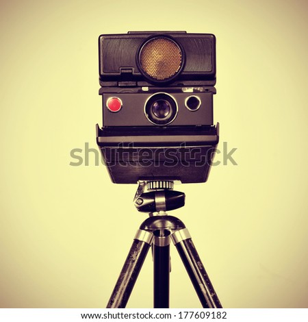 picture of an old instant camera in a tripod with a retro effect - stock photo
