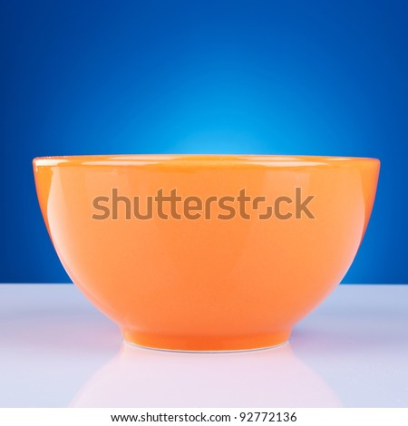 picture of an orange bowl against blue background - stock photo
