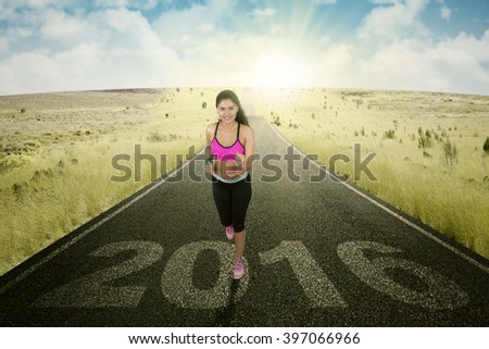 Picture of Asian female runner workout on the road with number 2016 on the asphalt