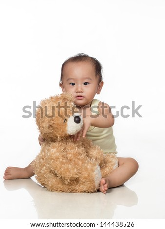 Picture of baby toddler hugging a generic stuffed teddy bear - stock photo