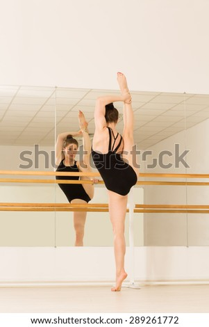 Picture of ballerina in studio. Slim and slender girl standing in front of mirror and training. - stock photo