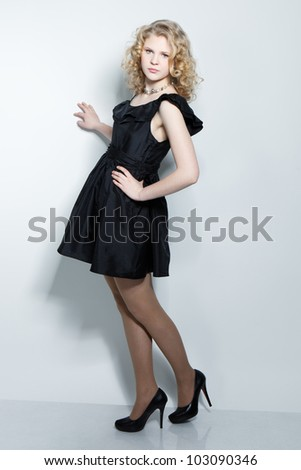 Picture of beautiful blonde teenage girl in black dress over gray