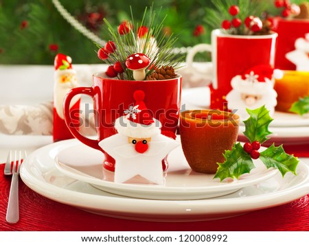 Picture of beautiful Christmas table setting, shining white plate with red cup for coffee decorated holiday dinner, branch of berry and santa claus star on festive dishware, New Year party, xmas eve