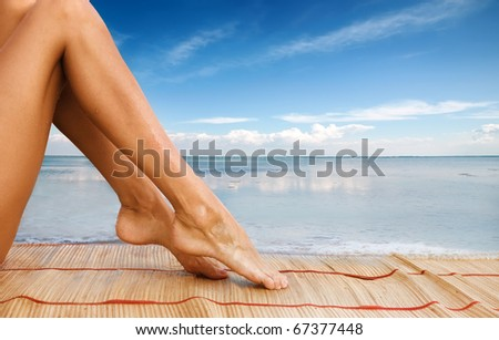 Picture of beautiful female legs on sea background - stock photo
