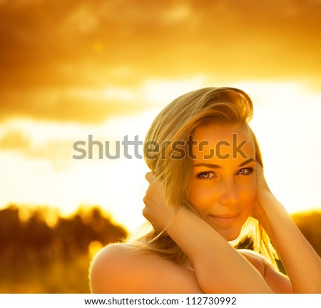 Picture of beautiful female over sunset, closeup portrait of cute romantic girl, attractive blond woman enjoying autumn yellow sunlight, pretty young lady outdoors rejoice of warm  weather fall - stock photo
