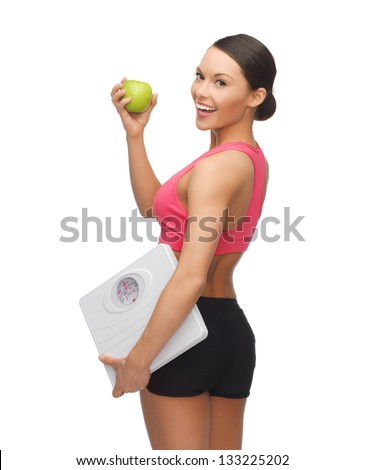 picture of beautiful sporty woman with scale and green apple - stock photo