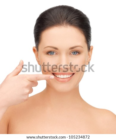 picture of beautiful woman pointing to teeth - stock photo
